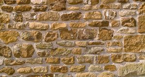 Honey-coloured stone wall background Royalty Free Stock Image