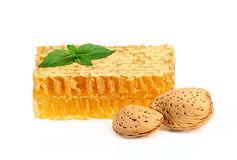Honey in the comb with almonds and a sprig of mint Royalty Free Stock Image