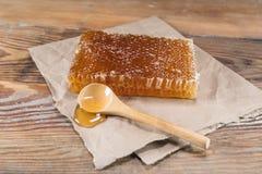 Honey Comb Block e colher de madeira no ângulo fotografia de stock