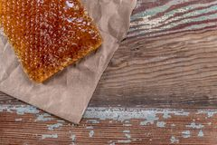 Honey Comb and Brown Paper Contrast With Copy Space Right. Over wooden table royalty free stock photos