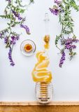 Honey comb and dipper with honey stains from jar with wild flowers on white background Royalty Free Stock Photos