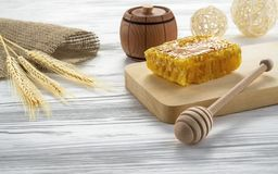 Honey comb and honey jar on wooden table stock image