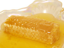 Honey in the comb, on a plate. Royalty Free Stock Images