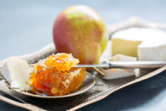 Honey comb, ripe pear and brie. Royalty Free Stock Images