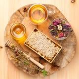 Honey comb, tea and herbs Stock Photos