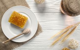 Honey comb on white plate and glass jar on wooden background royalty free stock photography