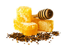 Honey comb with a wooden dipper and pollen Royalty Free Stock Image