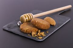 Honey and Cookies on a cardboard shale on a Black Background royalty free stock image