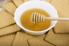 Honey and cookies. Close up view of honey dipper with honey dripping Stock Photo