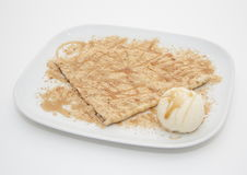 Honey crepe with ice cream. Crepe covered in sugar and drizzled with honey with vanilla ice cream on white chine plate Stock Photography