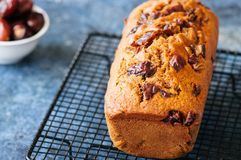 Honey and date spicy cake serving on a wire rack. Blue stone bac. Kground Stock Photography