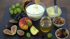 Honey is deposited on yogurt. Honey, figs, grapes, dried fruits, apple, yogurt for good breakfast stock video
