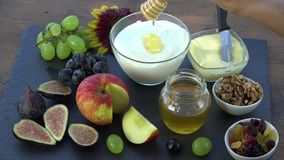 Honey is deposited on yogurt. Honey, figs, grapes, dried fruits, apple, yogurt for good breakfast for au good breakfast stock video