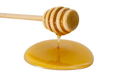 Honey and dipper. Honey dripping from a wooden honey dipper stock photography