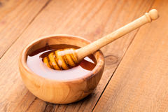Honey dipper. In a wooden bowl stock photo