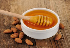Honey dipper with almonds Royalty Free Stock Image