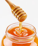 Honey dipper and full honey pot. Isolated on a white background royalty free stock image