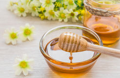 Honey dipper on glass bowl and jar Royalty Free Stock Image