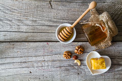 Honey and dipper. Honey in glass jar and dipper on rustic wood background Royalty Free Stock Photo