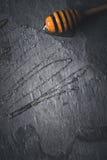Honey dipper with honey flourish on the dark stone background top view. Honey dipper with honey  flourish on the dark stone background top view vertical Royalty Free Stock Photos