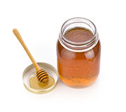 Honey dipper and honey in jar on white background Stock Photography