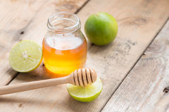 Honey dipper with honey and lime. Honey dipper with honey and lime on wood table Stock Images