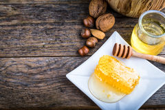 honey dipper and honeycomb, nuts of various kinds Royalty Free Stock Image
