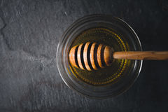 Honey dipper in the jar with honey on the dark stone table top view Royalty Free Stock Images