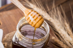 Honey dipper in a jar, on an old vintage wood background - close Royalty Free Stock Photography