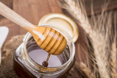 Honey dipper in a jar, on an old vintage wood background - close Stock Image