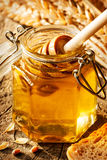 Honey dipper in a jar, wheat and bread on vintage wood Royalty Free Stock Photo