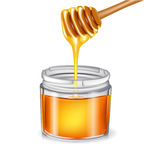 Honey with dipper pouring in jar Royalty Free Stock Image