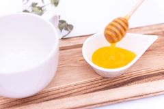 Honey dipper and a white can stock photography