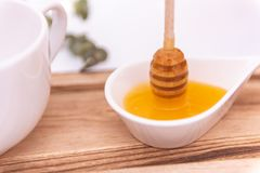 Honey dipper and a white can stock image