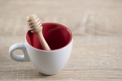 Honey dipper on the white coffee cup. On the brown table royalty free stock image