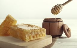 Honey dipper in Wooden jar and honey comb on wooden tray royalty free stock photos