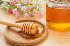 Honey dipper on wooden plate and jar Royalty Free Stock Photos