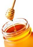 Honey Dipping con la miel en el tarro de cristal aislado en el backgr blanco Foto de archivo libre de regalías