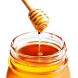 Honey Dipping con la miel en el tarro de cristal aislado en el backgr blanco Foto de archivo