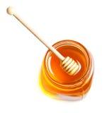 Honey Dipping con la miel en el tarro de cristal aislado en el backgrou blanco Fotografía de archivo libre de regalías
