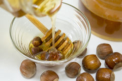 Honey dipping on hazelnuts next to a glass with honey Royalty Free Stock Photos