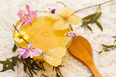 Honey and dried flowers on a lace tablecloth. Stock Images