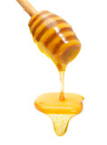 Honey drip from wooden dipper isolated Stock Photography