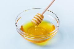 Honey drip from a wooden honey dipper in glass bowl on a blue background Stock Images