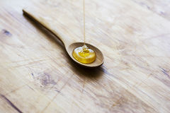 Honey driping into wooden spoon Stock Images
