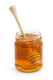 Honey dripper in a jar of honey. Over white Royalty Free Stock Photography