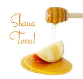 Honey dripping on apple isolated on a white. Rosh hashanah & x28;jewish New Year holiday& x29; concept. Traditional symbol. Text SHANA TOVA means HAPPY NEW Royalty Free Stock Image