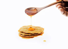 Honey dripping on breads from wooden spoon Royalty Free Stock Images