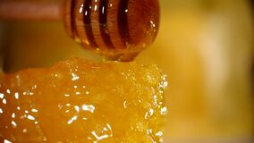 Honey dripping from honey dipper on honeycomb, over yellow background. Thick organic honey dipping from the wooden honey. Spoon stock video footage