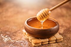 Honey dripping from honey dipper in wooden bowl. Healthy organic thick honey pouring from the wooden honey spoon. Closeup royalty free stock photos